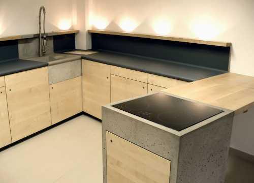 Küche - Ahorn, Beton und Linoleum; Die Arbeitsplatte ist mit einem strapazierfähigen Möbellinoleum belegt, welches sich fugenlos von der unteren Seite der Vorderkante über den Arbeitsbereich und die Rückwände bis unter den Regalsims zieht.