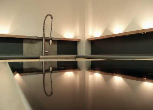 Küche - Ahorn, Beton und Linoleum; Im massiven Holzsims sind Steckdosen, Schalter und speziell entworfene, verstellbare Leuchten aus Edelstahl eingelassen. Ansicht indirekte Beleuchtung des Raumes;