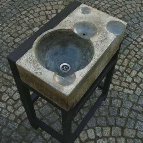 Badezimmerwaschbecken, mit eingegossenem Überlauf, Seifenschale und Ablagen; Verschiedentlich pigmentierter Betonguss, stahldraht- und glasfaser-verstärkt, geölt und imprägniert - auf grün-schwarz gebeiztem Holzgestell, 600 x 360 x 860 mm;